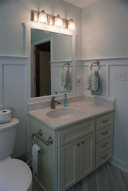 Bath remodel featuring custom mirror and wainscoting