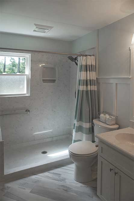 Master bath renovation with cultured marble shower walls and plank porcelain tile flooring