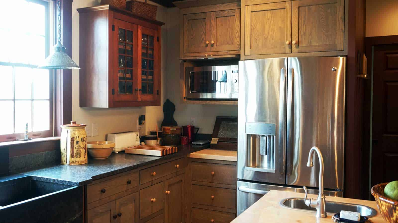 Early American inspired kitchen with cabinet doors designed to hide appliances