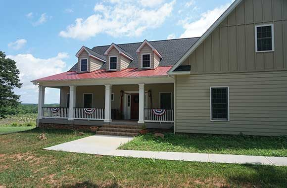 Front porch on custom built home with metal roof and dormers