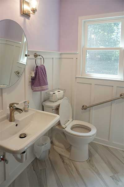 Custom bathroom remodel with accessible sink, safety grab bars, plank porcelain floors, and more