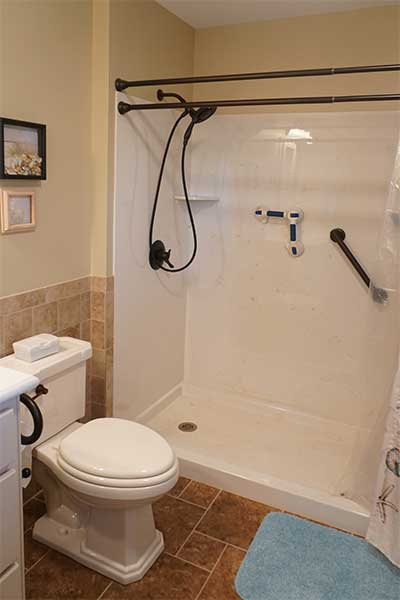 Cultured marble shower in this master bath includes bench seat, grab bars, and more