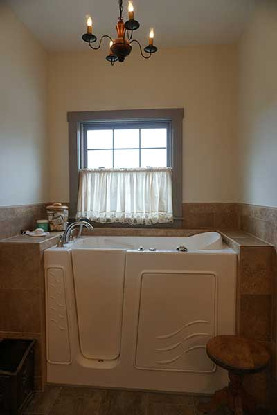 Beautiful custom tile surrounds this walk-in tub area